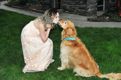 Girl in a dress kissing a dog